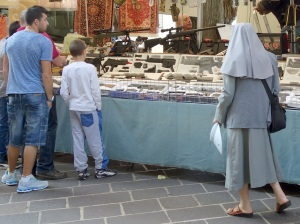 On Oct 5th, the day after the Feast Day celebration of St. Francis, there is a market set up in Assisi.  Here is a guy selling guns and a nun looking them over.