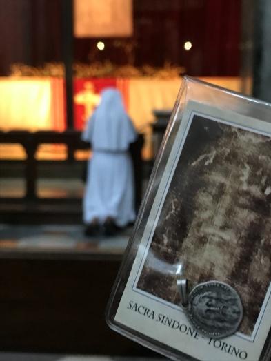 A nun kneels before the shroud.